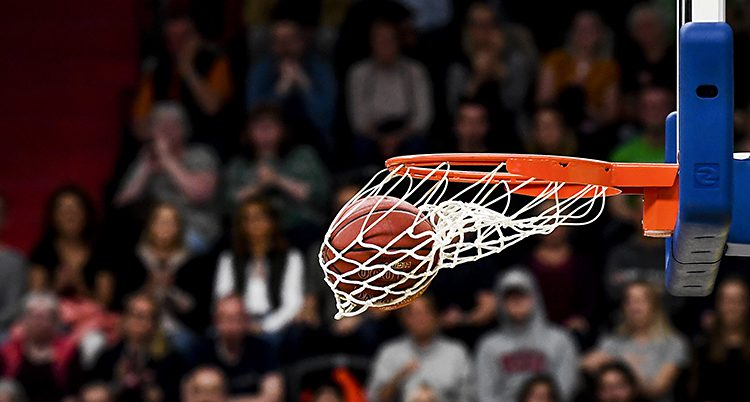 En basketboll som har åkt i en korg. Bollen ligger i nätet som svänger åt sidan. I bakgrunden syns publik.