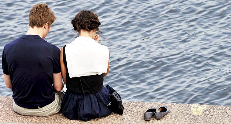 En man och en kvinna sitter bredvid varandra vid vattnet