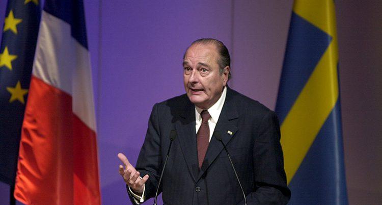Bilden är från år 2000. Den dåvarande franske presidenten Jacques Chirac står på en scen och pratar. Han har kostym och slips. I bakgrunden syns den franska flaggan och den svenska flaggan.