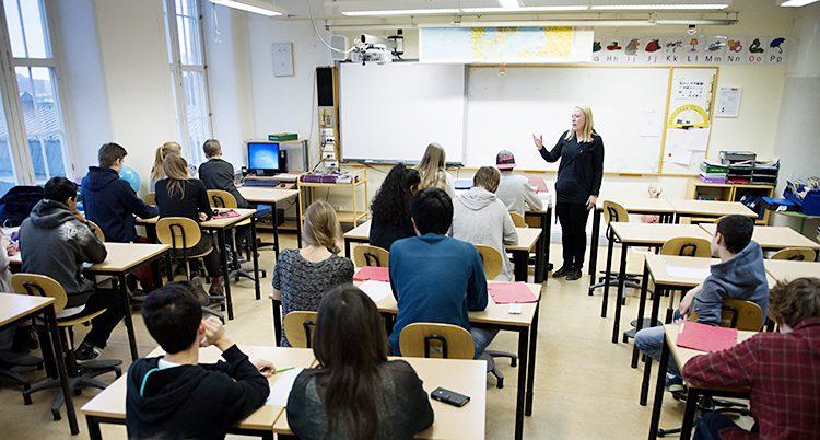 En lärare står längst fram i ett klassrum fyllt av elever