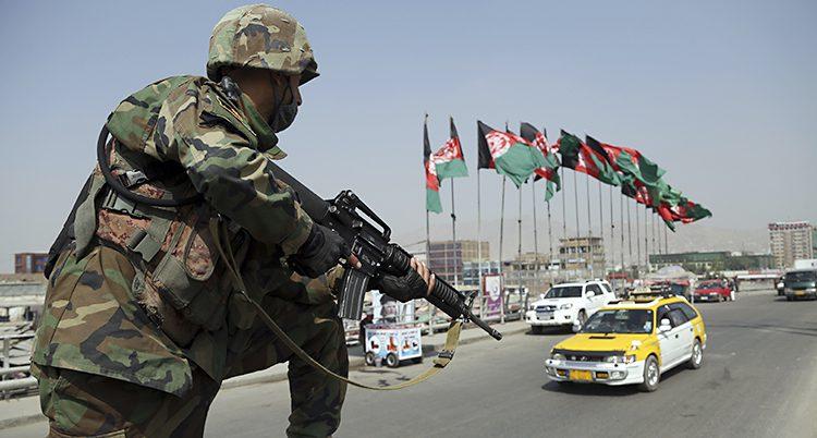 En soldat med vapen vaktar en gata med bilar och afghanska flaggor