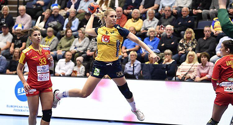 Vi ser en bild från en handbollsmatch. En kvinna hoppar upp. Hon har bollen i handen och laddar för ett skott. Hon har blå shorts och gul tröja. Bredvid henne syns två motståndare. De har röda kläder. I bakgrunden syns publiken.