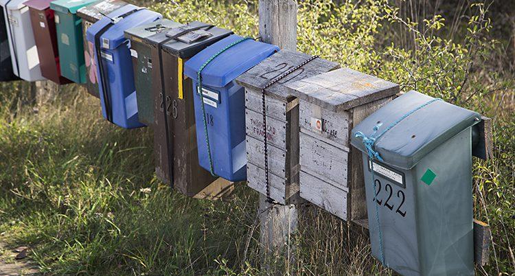 En rad med brevlådor i olika färg och material