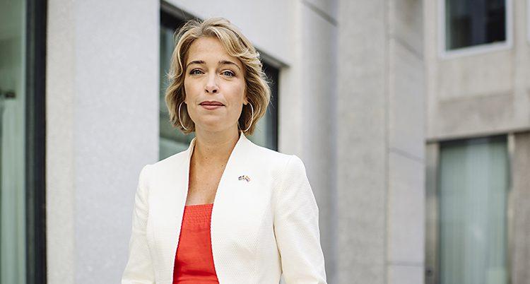 Politikern Annika Strandhäll står på en innergård. Hon tittar in i kameran. Hon har en röd tröja och en vit kavaj, och halvlångt hår.