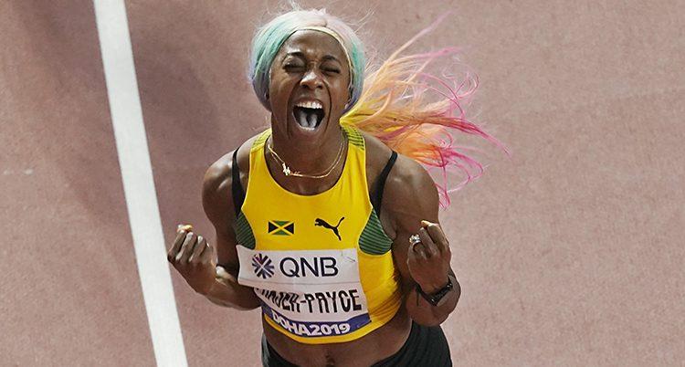 En kvinna från Jamaica firar att hon har vunnit. Hon har ett gult linne och en peruk i regnbågens färger. Hon knyter snävarna och skriker ut sin glädje.