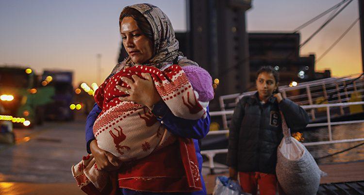 En kvinna bär ett litet barn i en sjal. En tjej kommer bakom med kassar och väskor