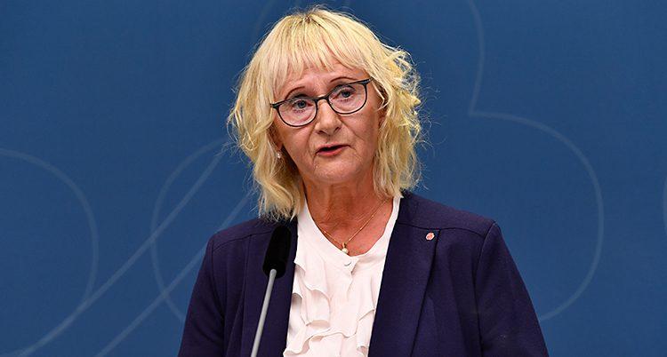 En kvinna pratar i en mikrofon. Hon har blont hår och glasögon. Hon har en vit blus och en mörk kavaj. Väggen i bakgrunden är mörkblå.