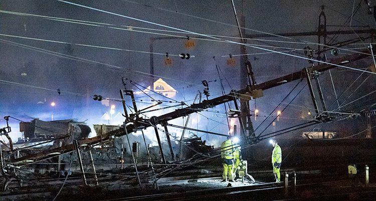 Det är kväll och mörkt ute. I bilden syns tågspår och några stora ledningar som har ramlat ner. Folk med gula kläder går runt och jobbar.