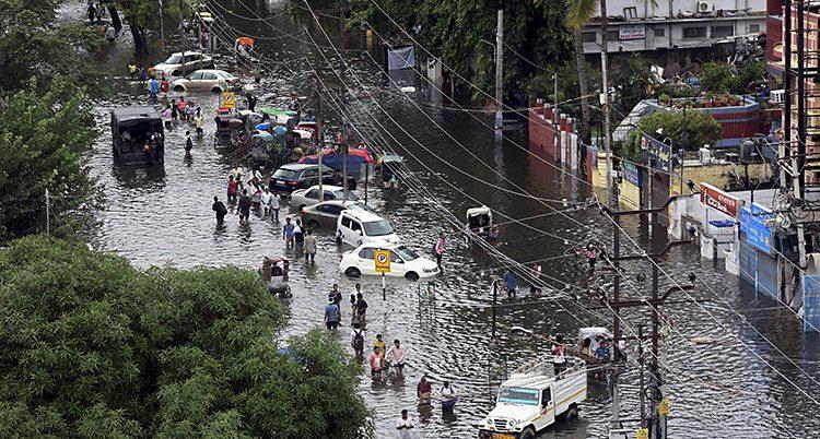 Människor går på en översvämmad väg i Indien.