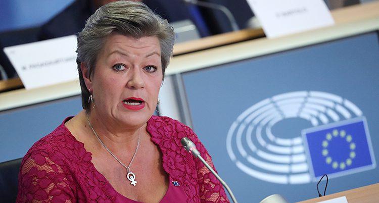 Ylva Johansson har röd spetströja och sitter vid ett bord med mikrofon
