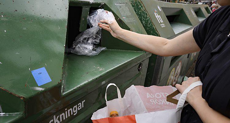 En kvinna slänger plast i en stor container på en återvinningstation.