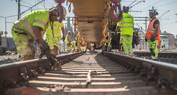 På bilden syns ett järnvägsspår. Flera arbetare håller på och jobbar vid spåret. De har på sig arbetshjälmar och kläder som lyser i gult.