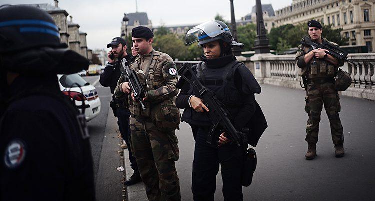 Flera poliser mot vapen och skottsäkra västar står vid en gata.