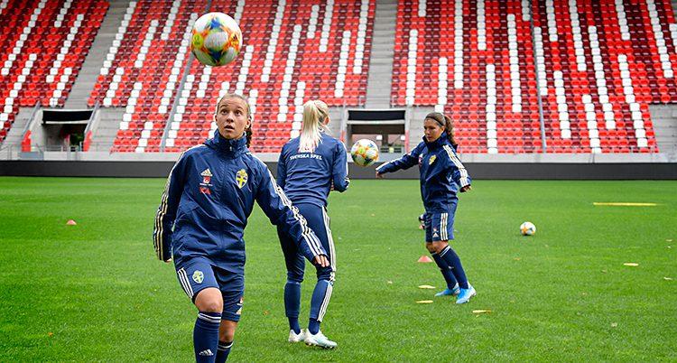 En bild från en träning med svenska landslaget i fotboll, damer. Tre spelare är på en fotbollsarena med tomma läktare. Spelarna har träningsoveraller på sig och tränar med bollar.