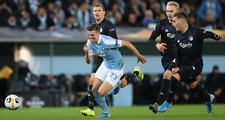 En bild från en fotbollsmatch. Flera spelare springer efter bollen. En av dem har ljusblå tröja. De andra har svarta tröjor.