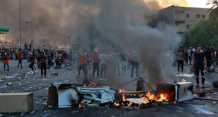 Brinnande bråte på en gata i Bagdad. Människor samlas bakom.
