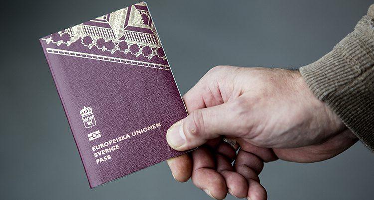 En hand håller i ett svenskt pass.