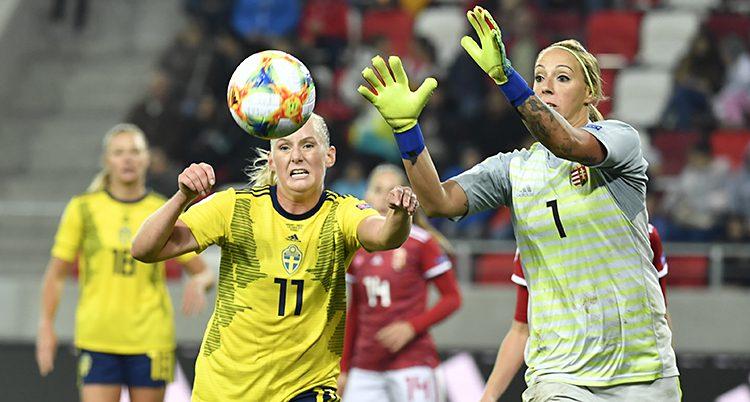 Två fotbollspelare närmar sig en fotboll som är i luften.