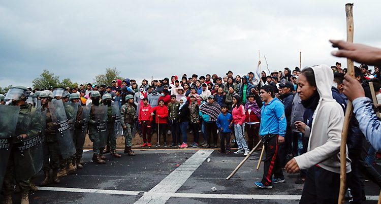 Arga människor står på en bäg. Soldater kommer emot dem.