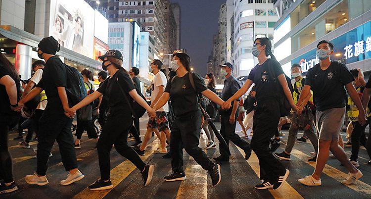Vi ser en bild från Hongkong. Folk går över ett övergångsställe. De håller varandra i händerna och har masker för ansiktet.