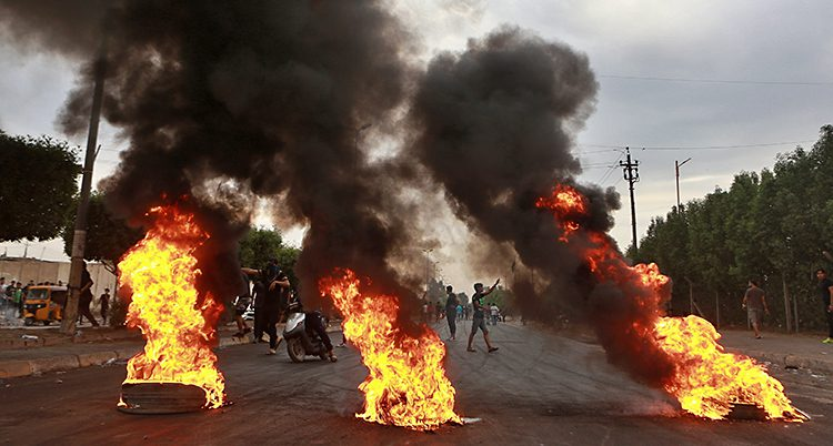 det brinner på marken på en väg. Bakom står människor som protesterar.
