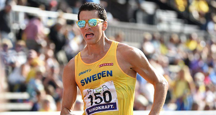 En man som tävlar i sporten gång. Han har solglasögon på sig och ett gult linne där det står Sweden.