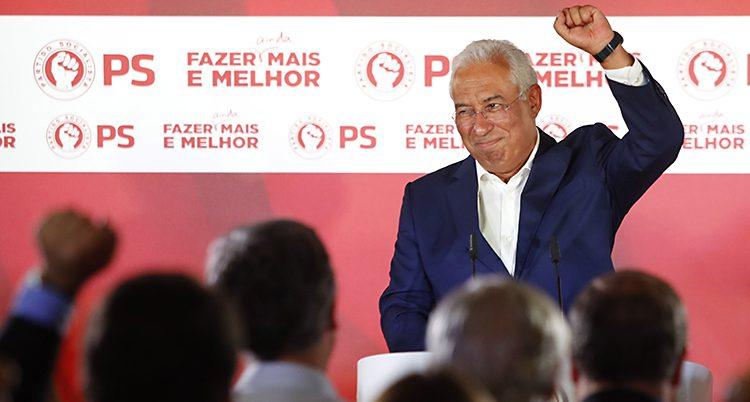Costas höjer armen och ler som en vinnare. Han står på en scen och tittar ut över en publik.
