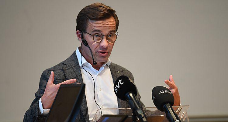 Ulf Kristersson håller ett tal. Han står och pratar i flera mikrofoner. Han gör gester med händerna medan han pratar. Han har glasögon, vit skjorta och en kavaj.