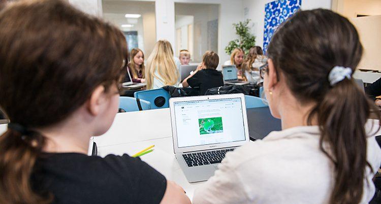 Elever sitter i ett klassrum. De har en dator framför sig.