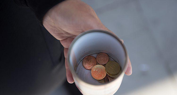 En hand håller i en mugg. Några mynt ligger i muggen.