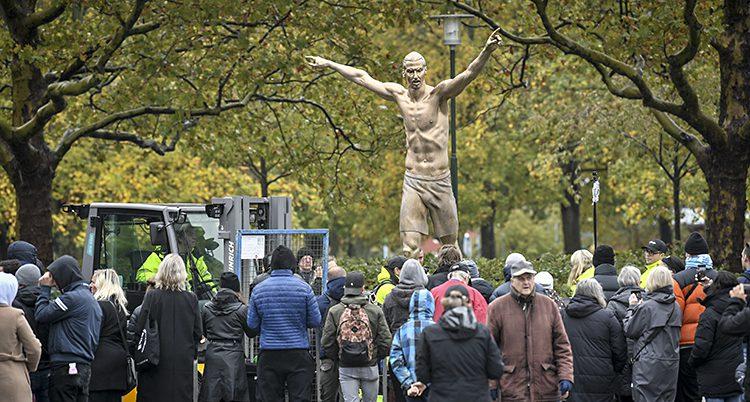 Många människor står framför en staty av fotbollspelaren Zlatan.
