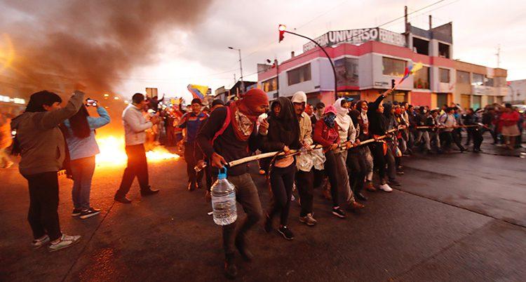 Det är skymning. Människor går i rad och håller i käppar framför sig. Många är maskerade. I bakgrunden brinner det och rök stiger mot himlen.