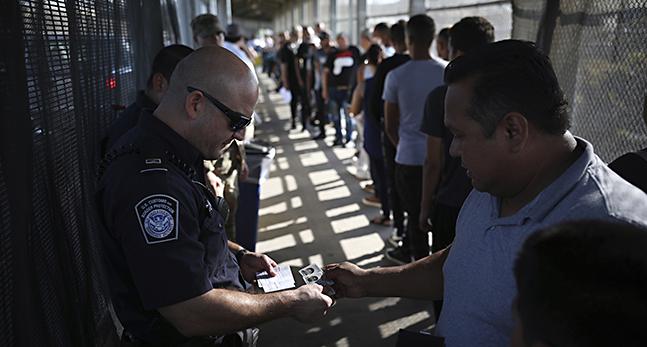 En polis tittar på en mans id-kort. Framför mannen ringlar kön lång. De omges av höga stängsel.