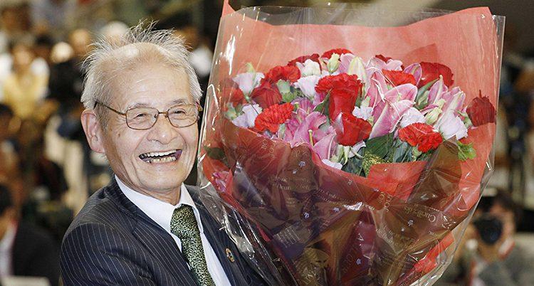 En äldre japansk man som ler. Han har glasögon, kostym och slips. I sin hand håller han en stor blombukett som han har fått.