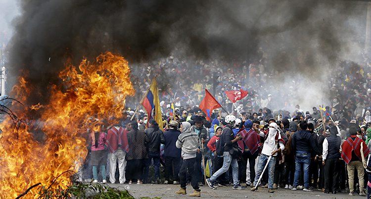 Flera tusen människor är ute på gatan. De har flaggor i händerna. En eld brinner. Det är mycket rök i bakgrunden.