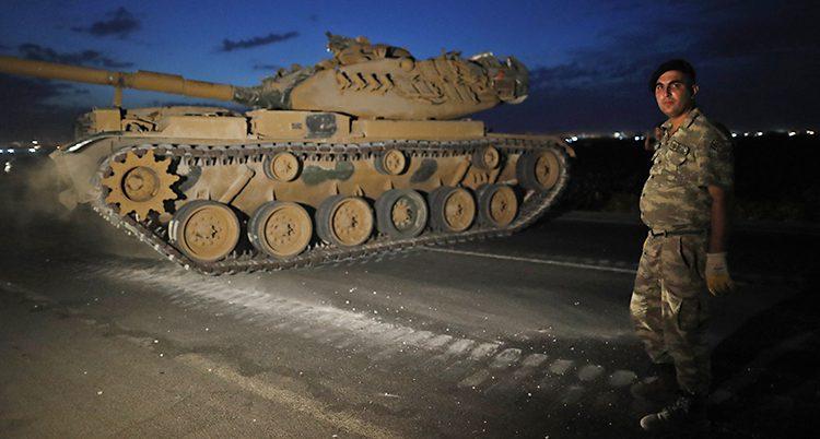 Bilden är tagen på kvällen eller på natten. Det är mörkt. Vi ser en bandvagn. En militär står bredvid bandvagnen. Han har en basker och kläder i kamouflage-färger.