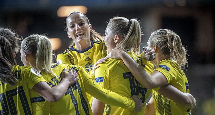 Svenska spelare i gula tröjor kramnar om Kosovare Asllani.