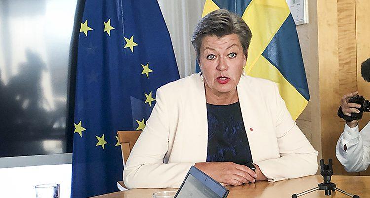Ylva Johansson pratar. Hon sitter vid ett skrivbord fram en svensk flagg och EUs flagga.