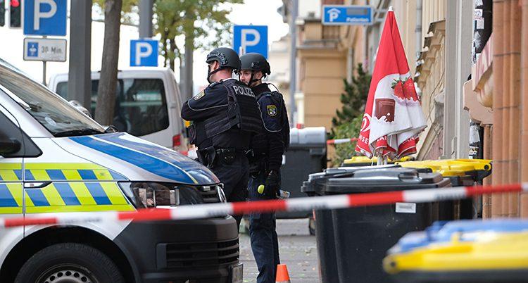 Två poliser står bredvid en polisbuss. Området är avspärrat med röd och vit tejp.