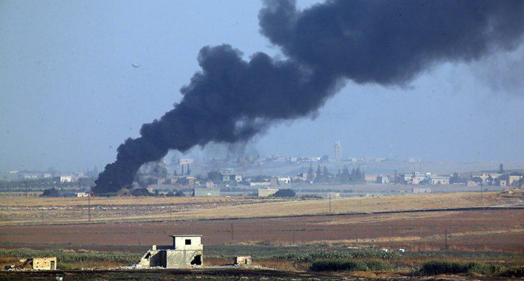 En bild över ett landskap med hur långt borta. Kraftig svart rök kommer från en av byarna.