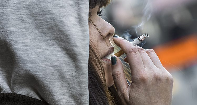 En nära bild på en kvinna som röker en cigarett.