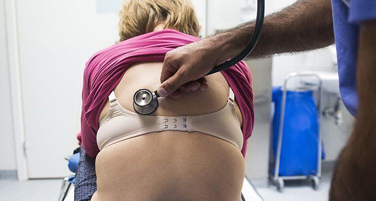 En läkare undersöker en kvinnas rygg med stetoskop.