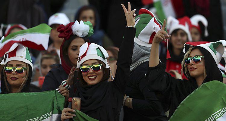 Kvinnorna har solglasögon och hattar i vitt, rött och grönt. De ser glada ut.
