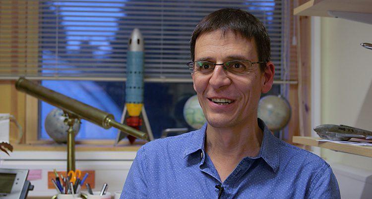 Ett porträtt på Didier Queloz. Han ser glad ut. I fönstret bakom honom står en modell av en raket.