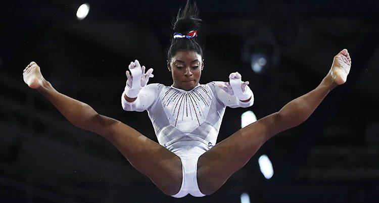 Simone Biles flyger i luften. Hon har båda benen utsträckta. Hon har en vita gymnastikdräkt och en svart knut i håret.
