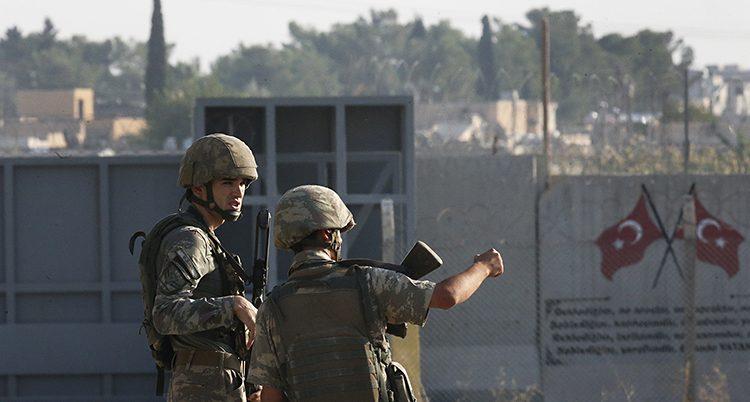 Två soldater står vid gränsen mot Syrien. De har vapen på sig. Turkiska flaggan syns i bakgrunden.