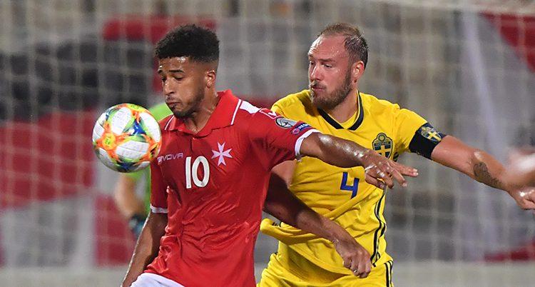 En spelare från Malta har bollen framför bröstet. Andreas Granqvist är bakom honom och försöker att komma åt bollen.