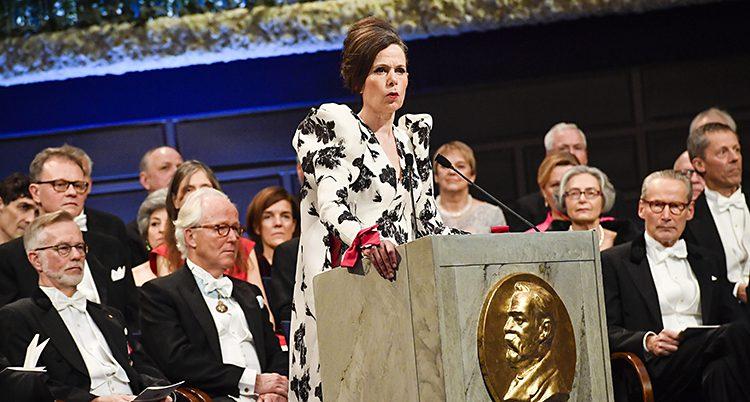Sara Danius står i en talarstol i en vit klänning med svart mönster. Bakom henne sitter herrar i frack.