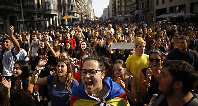 Människor med katalanska flaggor trängs på en gata.