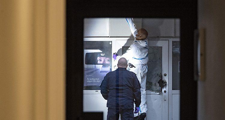 Två poliser undersöker dörren på ett polishus. Glaset på dörren har exploderat. En av poliserna har helt vita kläder. Den andra är klädd i mörkt blå poliskläder.